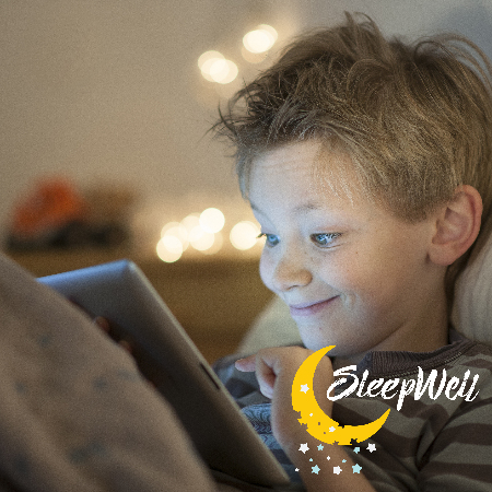 Boy in bed with electronic device at night