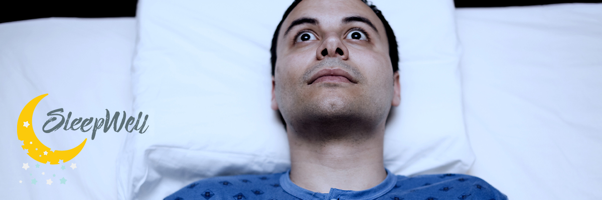 Man awake stressed in bed trying to sleep