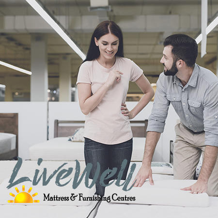 Happy couple shopping for mattress at Live Well Mattress and Furnishing Centres